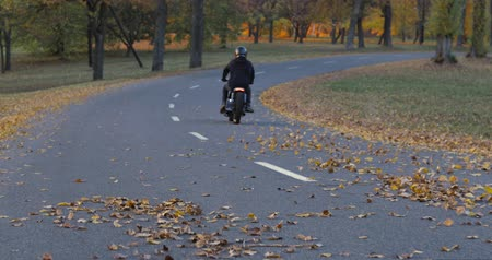 zvyk : Motorcyclist woman riding a bike cafe racer on an empty road in park. Yellow autumn foliage is scattered in different directions. 4K video shooting by handheld gimbal Dostupné videozáznamy