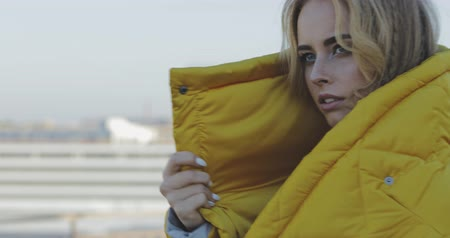 freckles : Young woman in winter jacket with golden hair and brown eyes looking at camera. Portrait of female model wearing long coat. Girl standing on roof of parking . 4k video evening urban city outdoor style Stock Footage