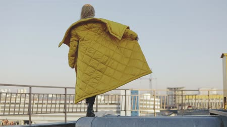 freckles : Young woman in winter jacket with golden hair and brown eyes looking at camera. Portrait of female model wearing long coat. Girl walking on roof. Slow motion video urban city style