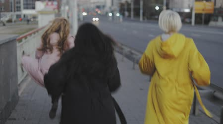 run down : Three beautiful multiracial girls have fun walking down the street , Female models wearing stylish jeans and long jacket coat. slow motion video steadicam shot