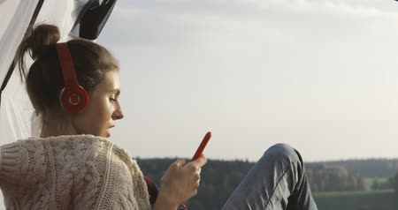 mobile music : Camping woman lying in tent . Close up of girl relaxing on vacation. Young happy female caucasian model in headphones listening to music and reading texting message on smart phone 4k video Stock Footage
