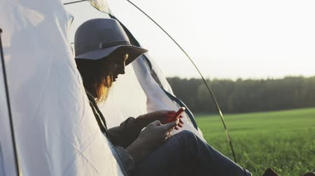 ouvir : Camping young woman sitting in camp tent . Happy girl relaxing on vacation. Young female caucasian model in headphones listening to music and reading texting message on smart phone Slow motion video Stock Footage