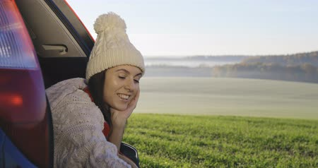 furgone : Young woman admiring the sunrise in trunk of car. Girl dressed in woolen socks taking photo on mobile phone against backdrop of forest panorama in fog . View from inside 4k video Filmati Stock