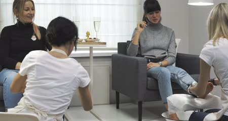 unha : Two women friends talking in spa beauty salon. Happy girls on bachelorette party. Female models sitting and waiting beauticians for pedicure. Slow motion video