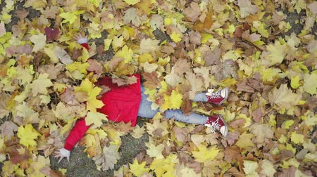 wrzesień : Cute girls playing with yellow leaves on beautiful autumn day. Happy children having fun in city park. Little female model dressed in red coat and hat lying over leaves and smiling. Slow motion video