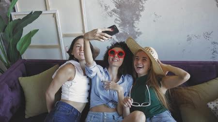 peruka : three female friends making selfies , young women grimasing and posing funny. Close up. Portrait shot. Indoor slow motion footage Wideo