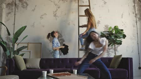 friendship dance : Slow motion of group mixed race young attractive women jumping on bed and having fun at home . Attractive multi ethnic joyful girls dancing on sofa at modern apartment loft