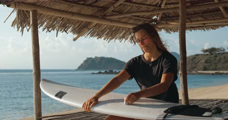 woman waxing : Girl surfer waxing her surfboard