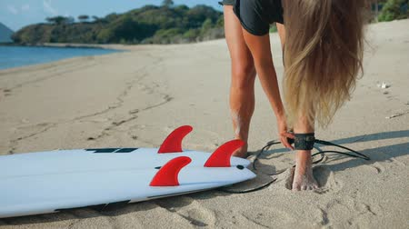 surfer paradise : Young surfer woman beginner fastens leash across leg