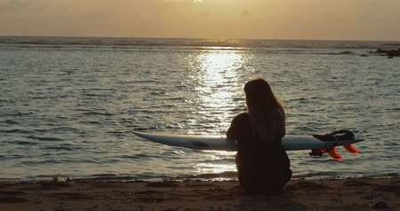 доска для серфинга : Silhouette of beautiful surfer girl on beach at sunset