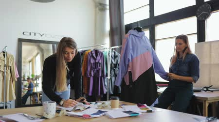 couture : Young female tailor workers, modeller and stylist discussing clothing design in workshop