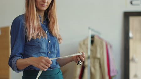 palce : Young woman fashion designer tailor unrolls the measuring tape. Slow motion