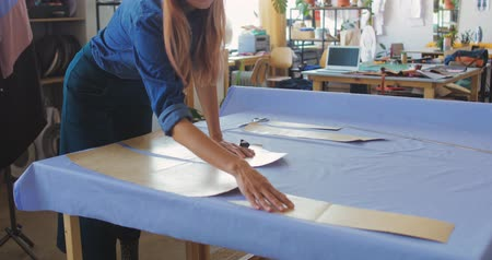 カット : Young woman cutting fabric by edge of paper pattern while making new item for seasonal fashion collection