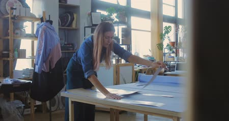 couturier : Young woman cutting fabric by edge of paper pattern while making new item for seasonal fashion collection