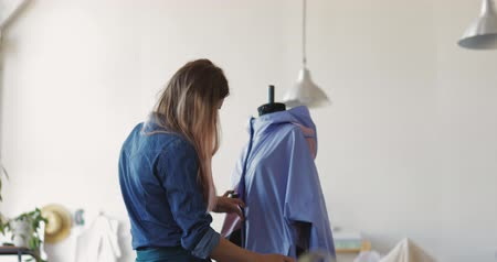 couturier : Professional well-dressed designer working on new model tailoring dress on mannequin in studio, talented dressmaker concentrated on making measures for sketch standing in showroom with clothing hanger