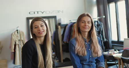 шить : Two young entrepreneur women, and fashion designer working on her atelier