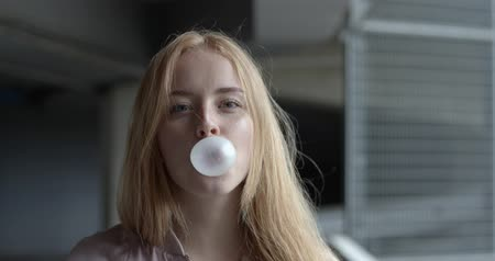 камедь : Closeup slow motion 4k video of young woman blowing bubbles from bubble gum