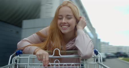 troli : Young woman having fun on the parking shopping mall. Happy funny girl rides on shopping cart. Customer with trolley near supermarket. 4k footage slow motion