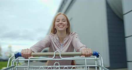 toló : Young woman having fun on the parking shopping mall. Happy funny girl rides on shopping cart. Customer with trolley near supermarket. 4k footage slow motion