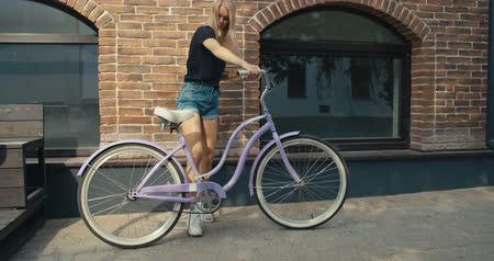 tevékenységek : Young modern woman riding bicycle in city. 4K slow motion video footage 60 fps