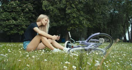 bicycle : Beautiful young woman sitting on grass and using phone on vintage bicycle background in summer park. 4K slow motion video footage 60 fps Stock Footage