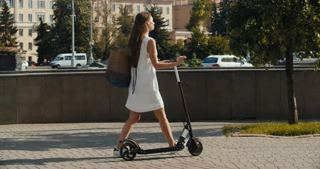lovas : Trendy woman, beautiful brunette girl riding electric scooter in modern city. 4K slow motion video footage 60 fps Stock mozgókép
