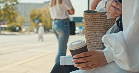 автобус : Young stylish woman waiting for the public transport while sitting at the modern tram station outdoors. close-up of female hand holding paper cup of coffee. 4K slow motion raw video footage 60 fps Стоковые видеозаписи