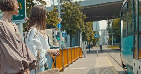 pravidelný : Group of young women waiting the tram. Stylish girls waiting for the public transport while at the modern station outdoors. 4K slow motion raw video footage 60 fps Dostupné videozáznamy