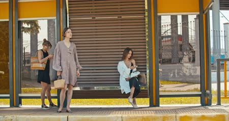 rendes : Group of young women waiting the tram. Stylish girls waiting for the public transport while at the modern station outdoors. 4K slow motion raw video footage 60 fps Stock mozgókép