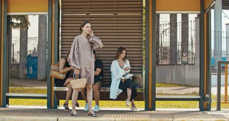 ônibus : Group of young women waiting the tram. Stylish girls waiting for the public transport while at the modern station outdoors. 4K slow motion raw video footage 60 fps Vídeos