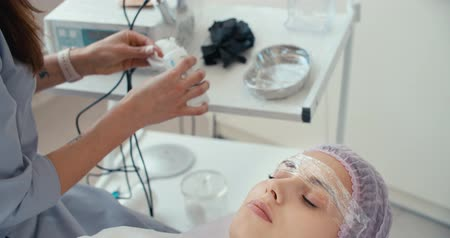 düzeltme : Microblading eyebrows work flow in a beauty salon. Cosmetician soaking alcohol sterile napkins. Semi-permanent makeup for eyebrows. 4K slow motion raw video footage 60 fps Stok Video