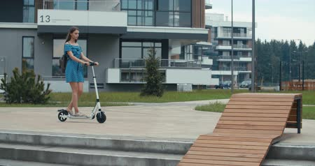 robogó : Attractive woman riding on the electric kick scooter. 4K slow motion video footage 60 fps Stock mozgókép