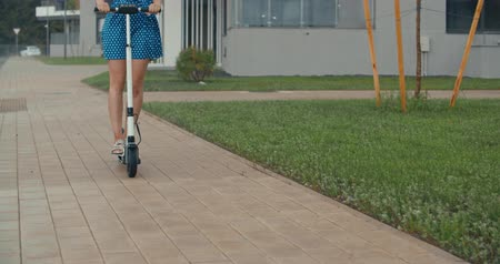 andar : Rainy day. Attractive girl returning home with the electric kick scooter. 4K slow motion raw video footage 60 fps Vídeos
