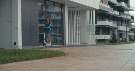 andar : Rainy day. Attractive girl riding the electric kick scooter to work or study. 4K slow motion raw video footage 60 fps