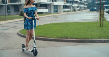 portaretrato : Rainy day. Attractive girl riding the electric kick scooter from home to work or study. 4K slow motion raw video footage 60 fps
