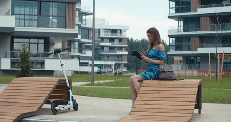 lezer : Woman sitting on bench among urban space and reading ebook using digital reader. Attractive girl with electric kick scooter. 4K slow motion raw video footage 60 fps Stockvideo