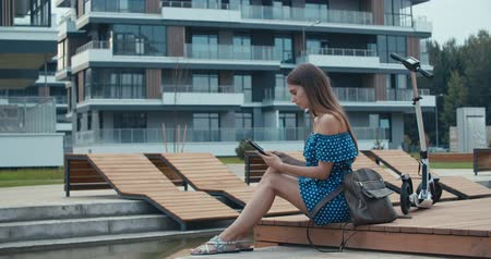 portátil : Woman sitting on bench among urban space and reading ebook using digital reader. Attractive girl with electric kick scooter. 4K slow motion raw video footage 60 fps Vídeos