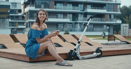 ebook : Woman sitting on bench among urban space and reading ebook using digital reader. Attractive girl with electric kick scooter. 4K slow motion raw video footage 60 fps Stock Footage