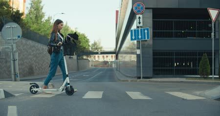 bouledogue français : Jeune femme passe sur le passage pour piétons. Girl riding the electric kick scooter with dog in city street from home to work or study. Séquences vidéo au ralenti 4K 60 ips