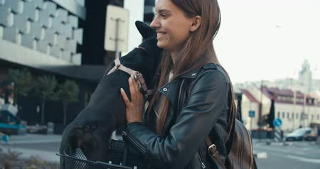 buldok : Young casually dressed woman holding her adorable French bulldog puppy. Close up shot city street in background. 4K slow motion raw video footage 60 fps