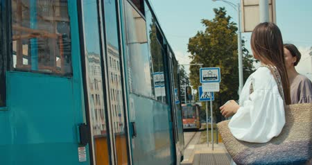安価な : Group of young women enter the tram. Stylish girls waiting for the public transport while at the modern station outdoors. 4K slow motion raw video footage 60 fps 動画素材