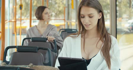 goedkoop : Girl sitting in tram using touchpad for chatting in social networks via free wifi connection, young woman reading e-book on portable pc in public transport. 4K slow motion raw video footage 60 fps