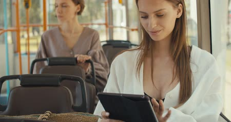 pravidelný : Girl sitting in tram using touchpad for chatting in social networks via free wifi connection, young woman reading e-book on portable pc in public transport. 4K slow motion raw video footage 60 fps