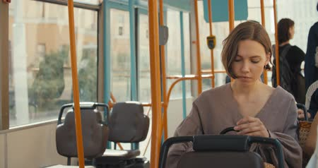 inside bus : Girl sitting in tram , young woman enjoying public transport. 4K slow motion raw video footage 60 fps
