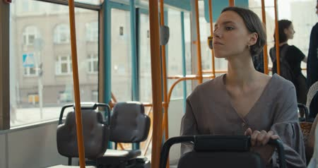 europeu : Girl sitting in tram , young woman enjoying public transport. 4K slow motion raw video footage 60 fps