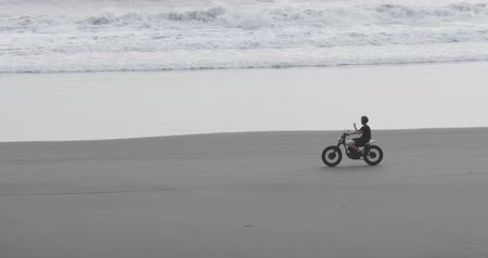 utcai : Handsome man biker driving his motorcycle cafe racer on the beach along the ocean during sunset. 4k video shooting by handheld gimbal
