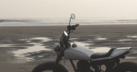 deriva : Vintage custom motorcycle cafe racer stands on beach bali