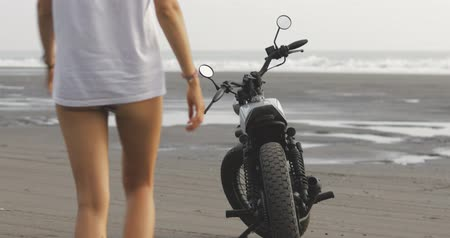 дрейф : Pretty girl wearing white clothes sits down on vintage custom motorcycle cafe racer traveling and having fun. Young female biker woman posing on beach bali. 4k video shooting by handheld gimbal Стоковые видеозаписи