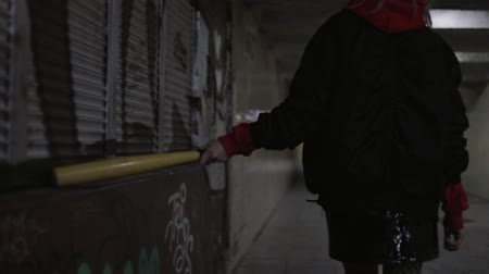 életmód : Sporty swag girl with baseball bat is walking in tunnel