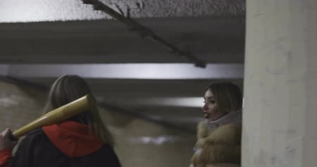 modelo de moda : Sporty swag girl with baseball bat is walking in tunnel